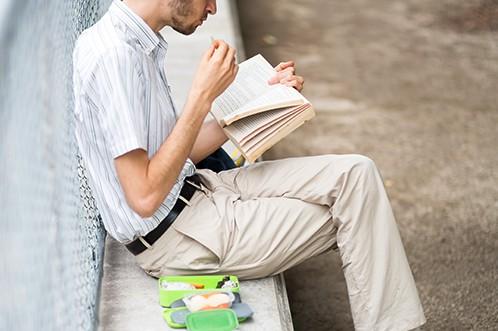 お食事しながら本を読む男性