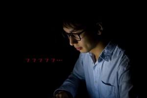 暗闇でPCを使う男性