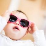 大きなサングラスをかける赤ちゃん