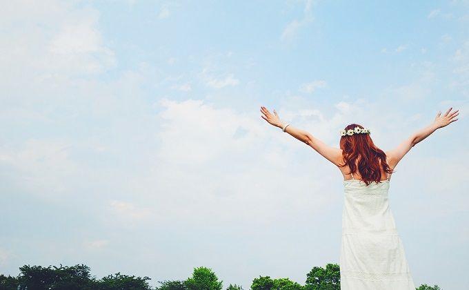 空に向かって手を広げる女の子