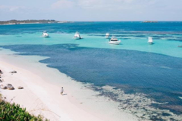 海と5隻のボートを眺めながら砂浜を歩く人