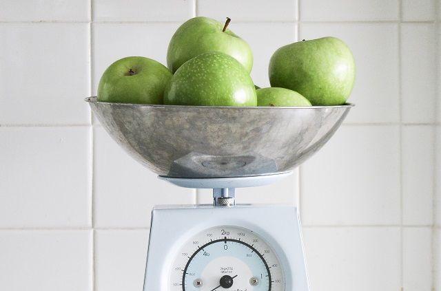 計りにのせた青リンゴ