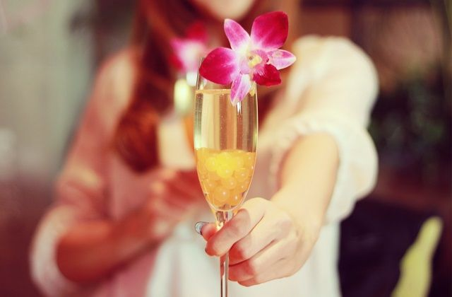 花の飾りがついたお酒を差し出す女の子