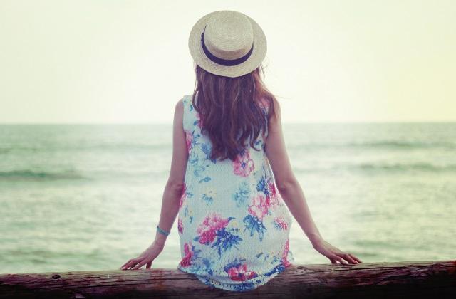 丸太に座って海を眺める女の子