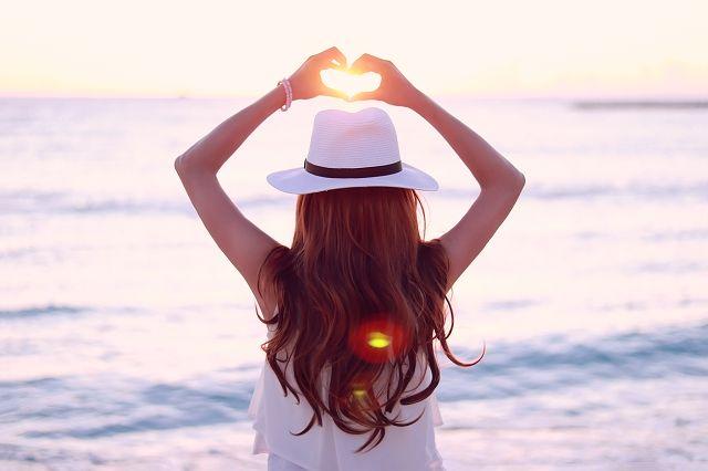 夕陽にハートの手をかざす女の子