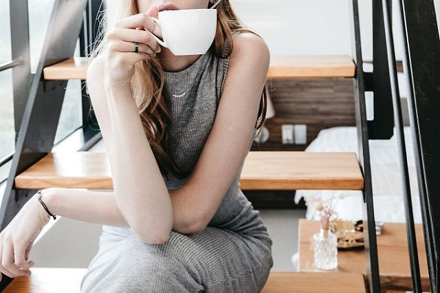 足を組みカップを手にする女性