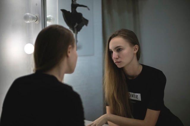 鏡をのぞき込む女性