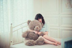 ベッドでテディベアを抱きかかえる女の子