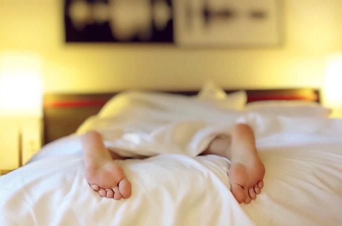 ベッドに突っ伏す人の足
