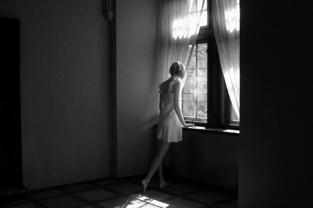 窓の外を見下ろす女性