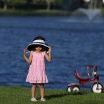 帽子を深く被る女の子と三輪車