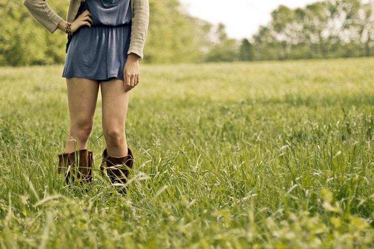 芝生に立つブーツをはいた女の子