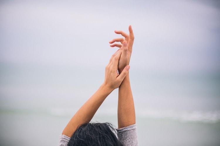 海、腕を伸ばす女性