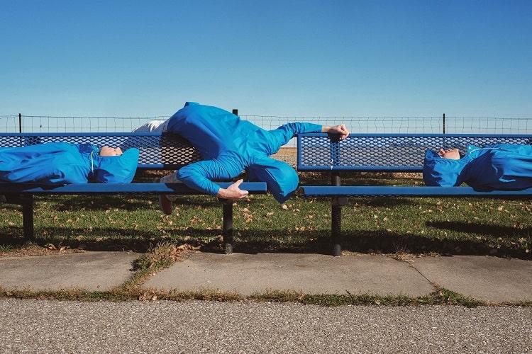 ベンチに横たわる3人の青い人