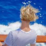 ブロンドのショートヘアで海を眺める