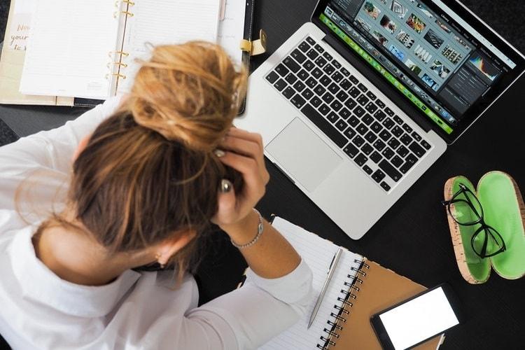 パソコンを前に頭を抱えるお団子頭の女性