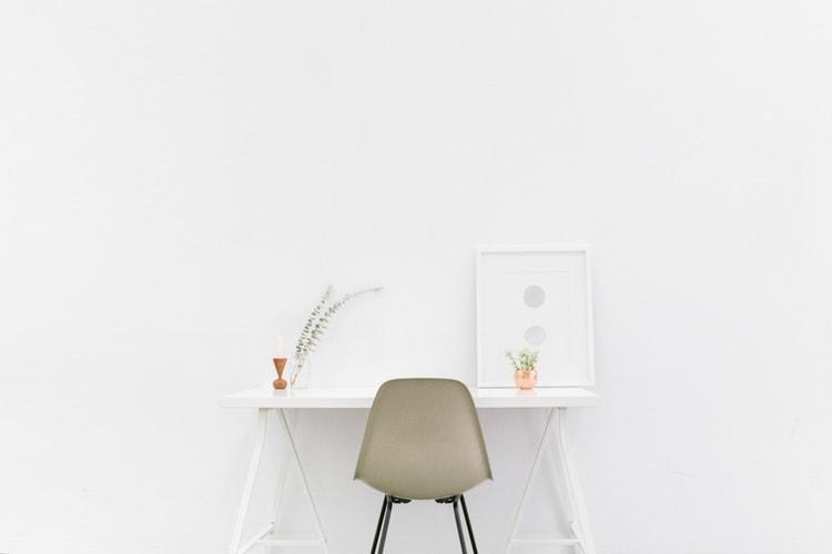 白い壁と白い机、ベージュと黒のイス