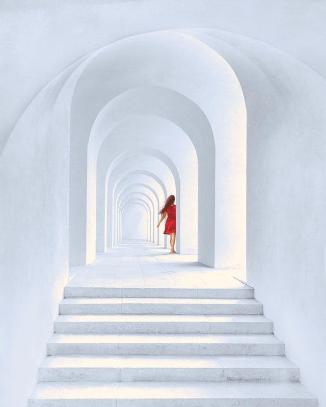 白い建物内アーチと赤い服の女の子